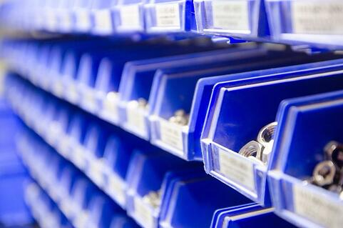 Rows of blue plastic storage bins containing stocks of parts and components, such as screws, bolts and nuts, in an industrial or commercial warehouse shot with selective focus