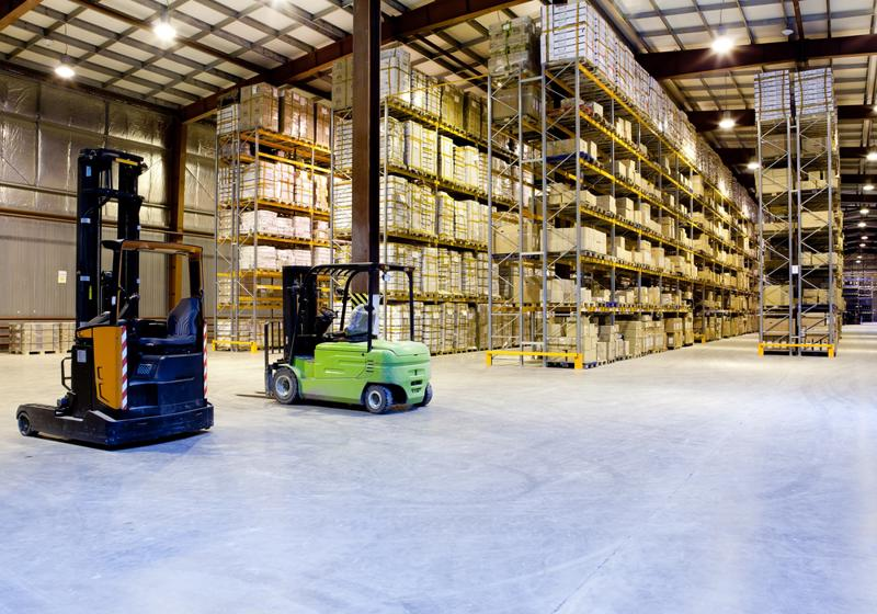 Two forklifts drive through a warehouse.