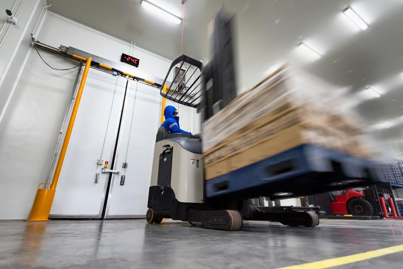 A forklift operator drives a pallet of goods through a cold storage facility.